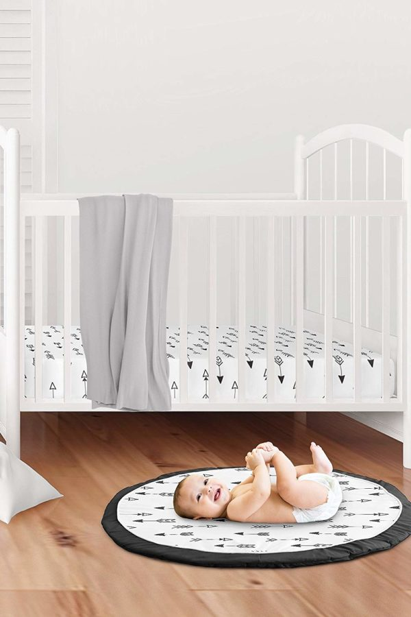 baby on black and white round baby mat with cot in background and grey rug
