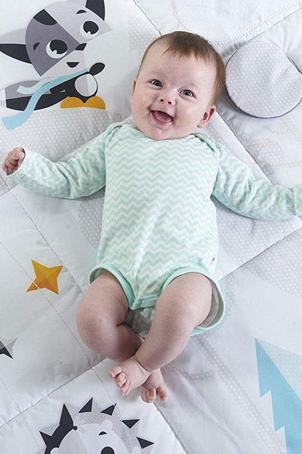 simling young baby on activity mat