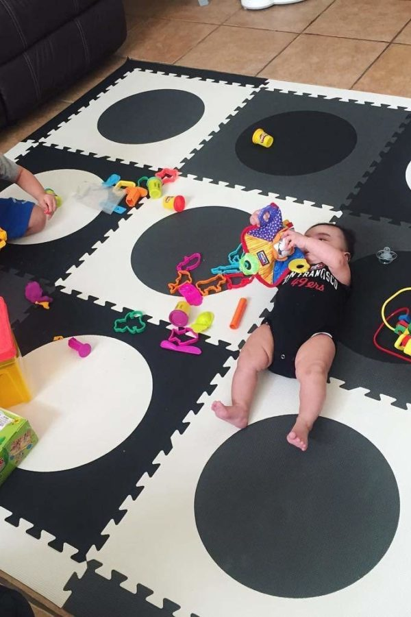 Baby and Toddler on black and white playmat with toys