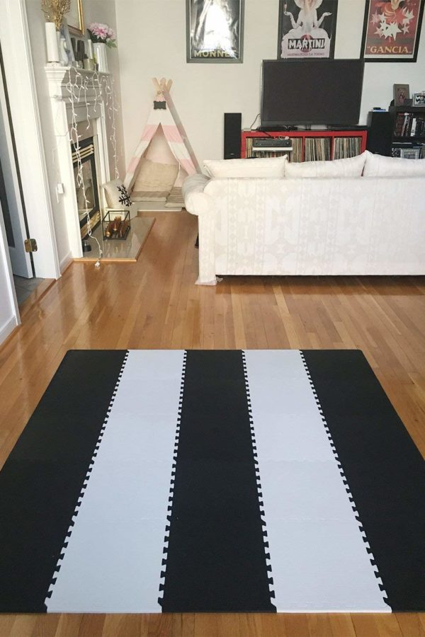Black and white interlocking tiles playmat, floor boards, couch
