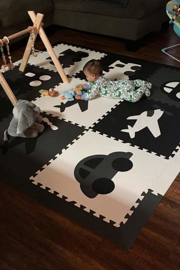 baby crawling on black and white transport themed playmat with 9 squares