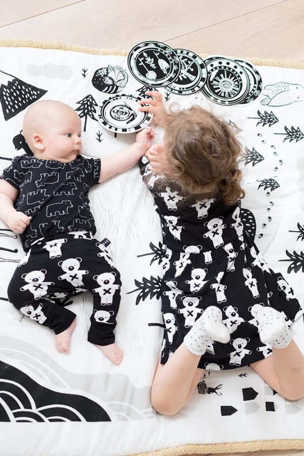 baby and sister on black and white playmat