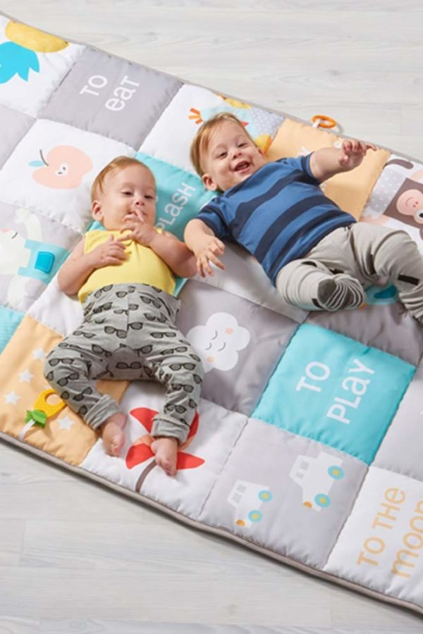 twins on a large colorful playmat