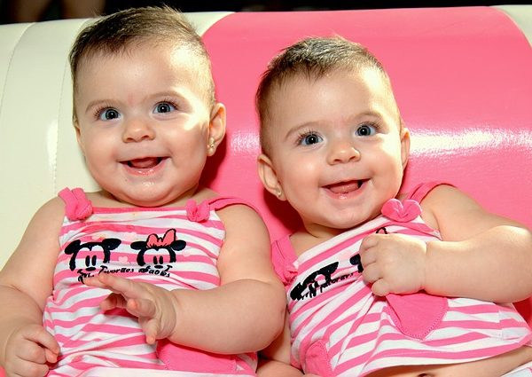 smiling twin girls with horizontal striped pink and white tops