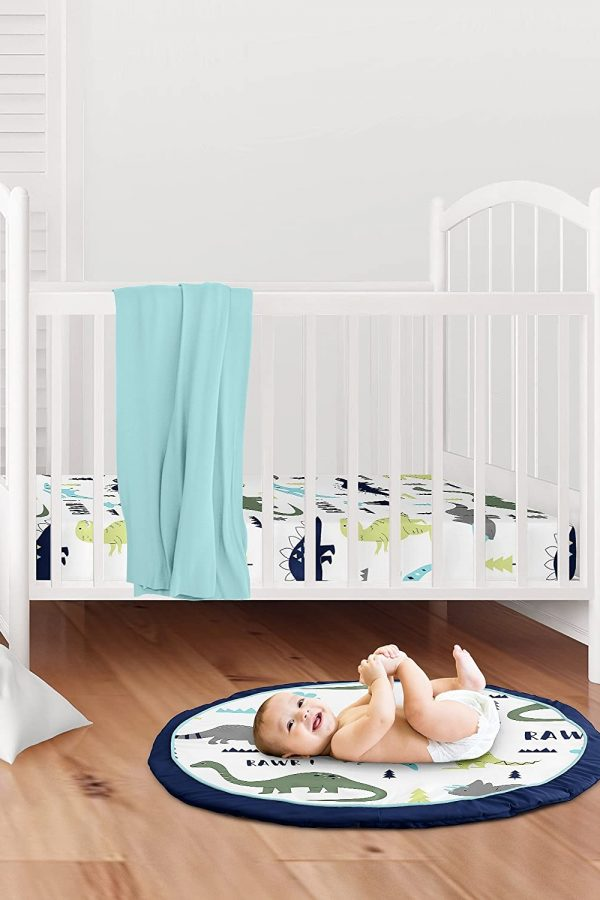 Smiling baby on round dinosaur themed playmat on floor with cot in background