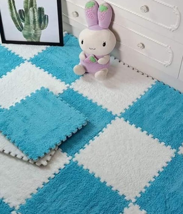 light blue and white interlocking playmat with picture frame and toy on floor leaning against bedroom draws