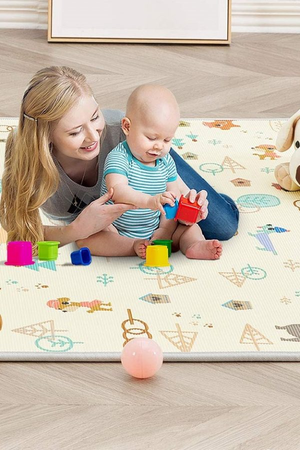Mum and bbaby on reversible playmat playing with toys