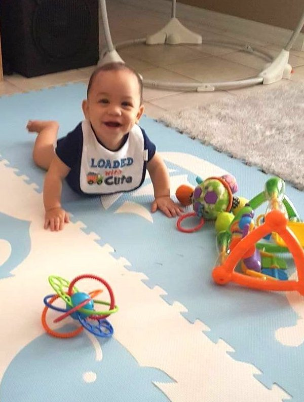 Smiling baby with toys on nautical playmat