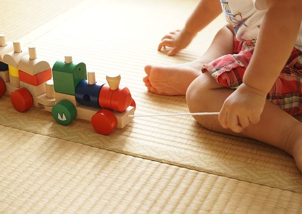 toddler pulling along wooden train on playmat