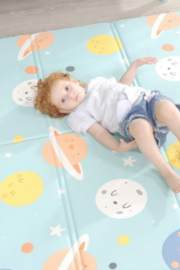 child laying on soft foam space playmat