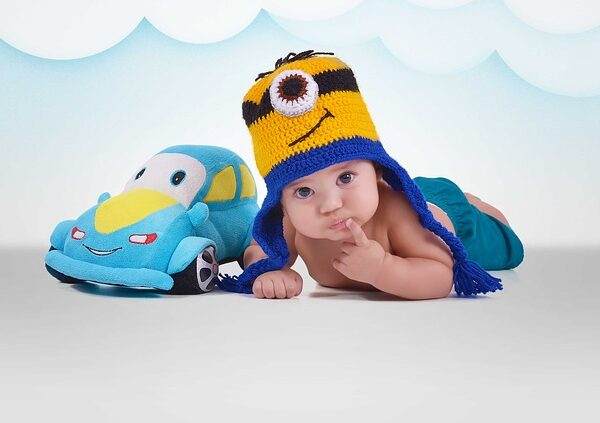baby wearing beanie on tummy next to toy car cushion