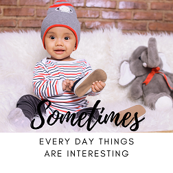 Toddler sitting on white fluffy couch holding his shoe and sitting next to soft elephant toy